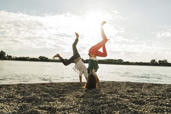 Playful young couple doing handstands by the riverside — Stock Photo