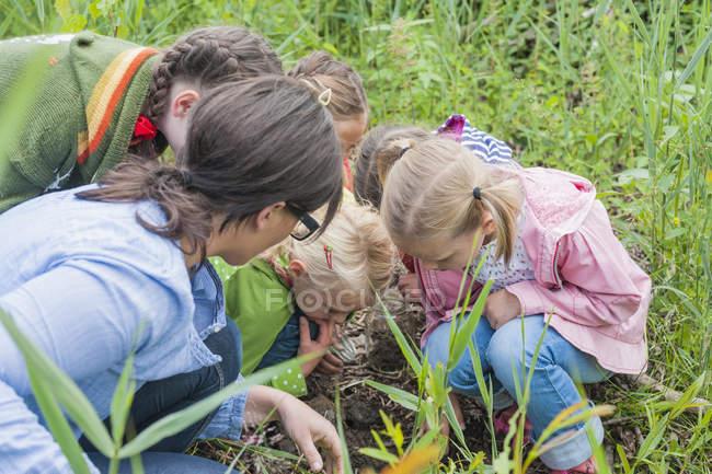 Kinder und Lehrer, die Würmer in der Natur sammeln — Stockfoto