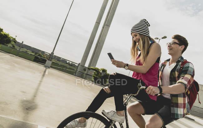 Jovem casal feliz com telefone celular juntos em uma bicicleta — Fotografia de Stock