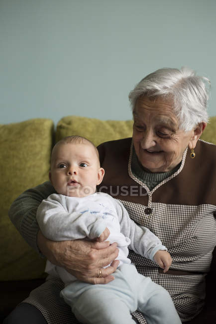 Portrait of great-grandmother sitting on couch with her great-grandson — Stock Photo