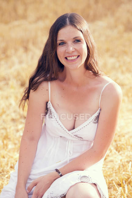 Portrait of smiling young woman on a stubble field — Stock Photo