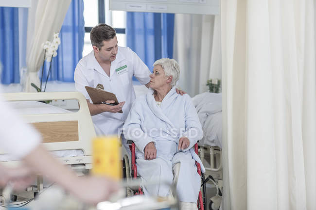 Nurse with elderly female patient in wheelchair — Stock Photo