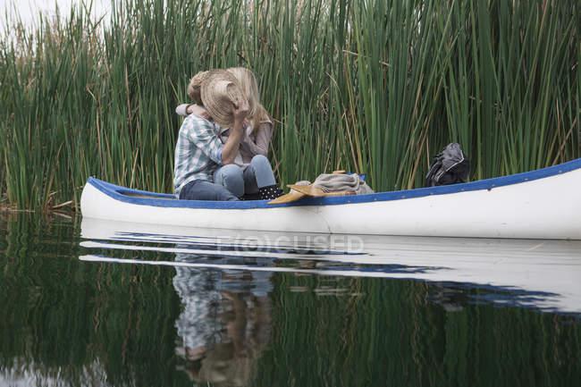 Jeune couple s'embrassant dans un canot sur un lac, se cachant derrière le chapeau de paille — Photo de stock