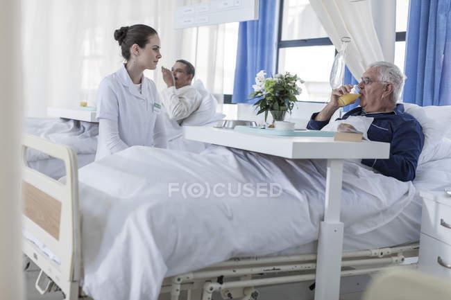 Krankenschwester betrachtet Seniorin im Krankenhausbett — Stockfoto