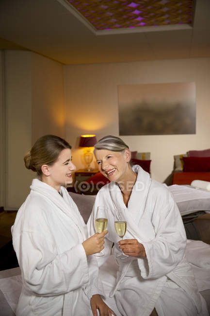 Happy senior woman and adult daughter in bathrobes clinking champagne glasses — Stock Photo