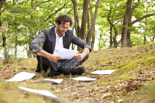 Businessman sitting in forest reading documents — Stock Photo