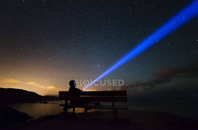 España, Ortigueira, Loiba, silueta de un hombre sentado en el banco bajo el cielo estrellado con rayo azul - foto de stock