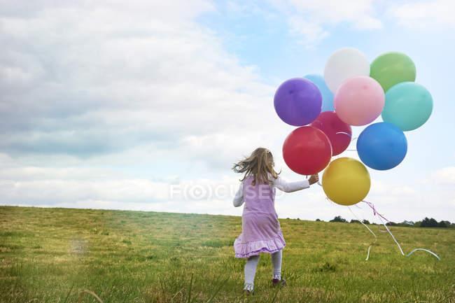 Visão traseira da menina pré-escolar com balões correndo no prado — Fotografia de Stock