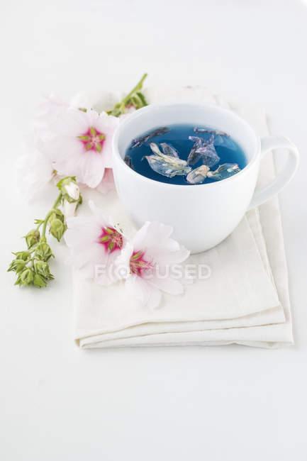 Tasse de thé de Mallow et fleurs sur tissu — Photo de stock