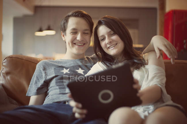 Teenage couple with digital tablet at home — Stock Photo