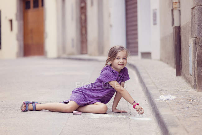 Little girl drawing with crayon on the street — Stock Photo