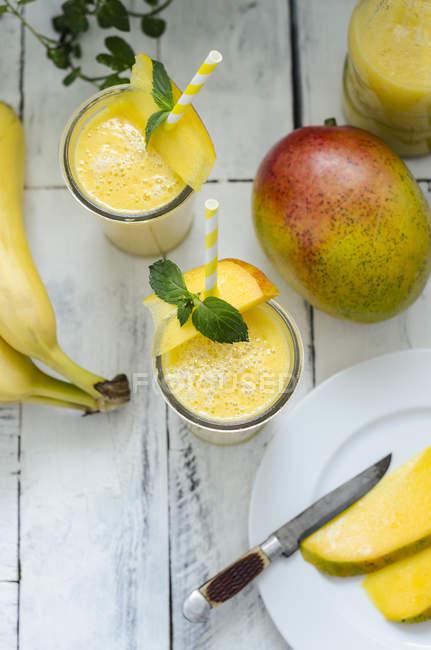 Deux verres de smoothie banane mangue sur une surface en bois blanche avec des ingrédients — Photo de stock