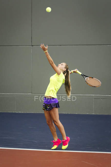 Young woman playing tennis in an indoor tennis center — Stock Photo