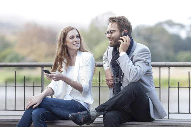 Couple with smartphones on a terrace — Stock Photo