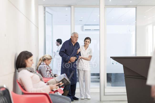 Krankenschwester unterstützende Patienten im Wartebereich — Stockfoto