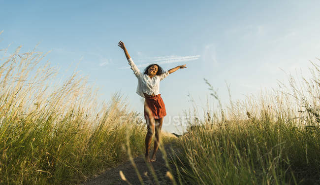 Young woman standing with outstretched arms on path in field — Stock Photo