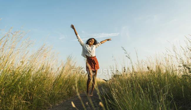 Junge Frau mit ausgestreckten Armen auf Pfad im Feld — Stockfoto