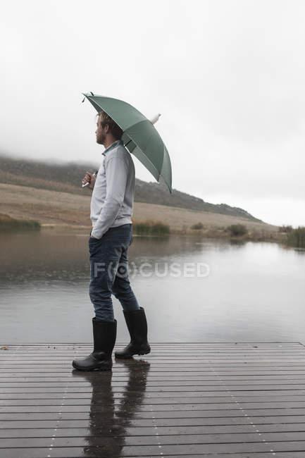Homem andando na chuva no calçadão de madeira com guarda-chuva verde — Fotografia de Stock