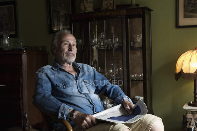 Senior man with newspaper relaxing at home — Stock Photo
