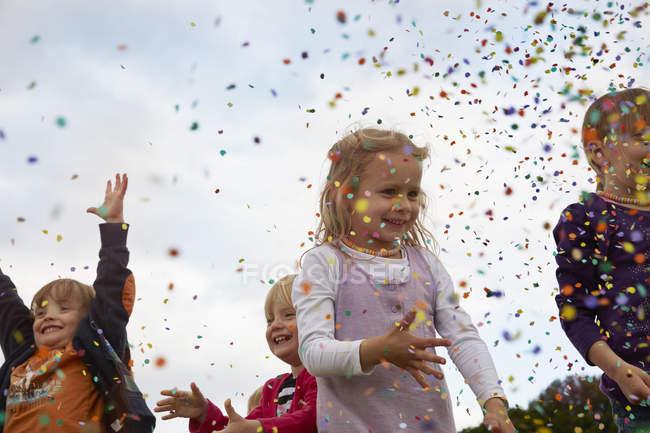 Маленькі діти, кидаючи конфетті лука у сільській місцевості — стокове фото