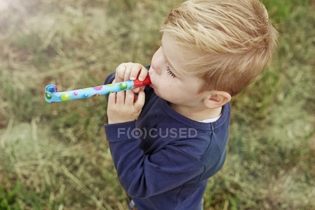 Little boy with party blowout on a meadow — Stock Photo