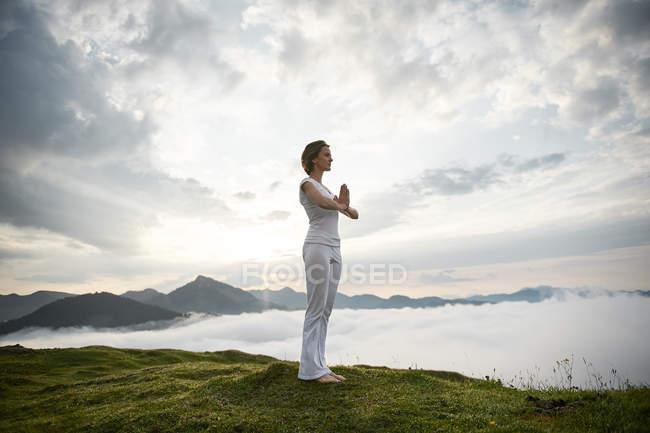 Austria.kranzhorn, Mitte erwachsene Frau praktiziert Yoga auf Berggipfel — Stockfoto