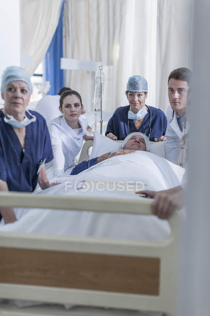 Krankenhauspersonal stehend am Bett mit Patienten — Stockfoto