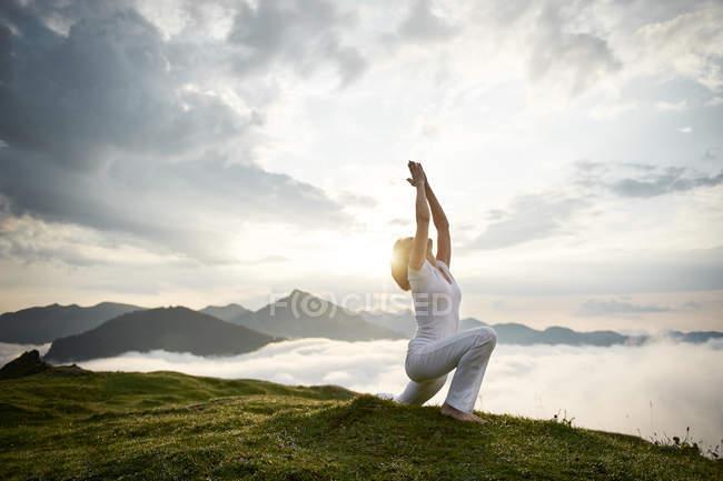 Austria. Kranzhorn, Mid adult woman practising yoga on mountain top — стоковое фото