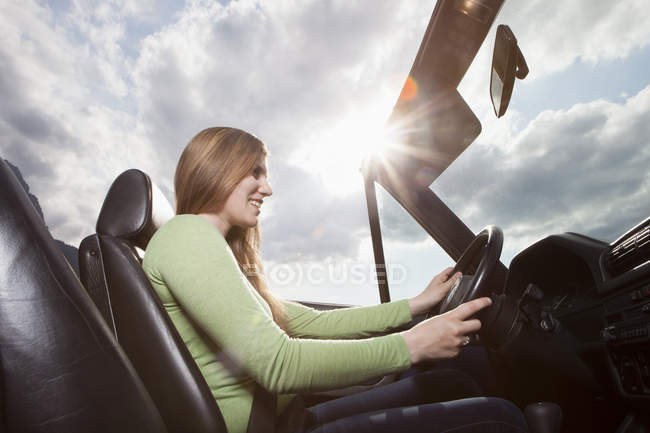 Happy woman driving in a convertible — Stock Photo