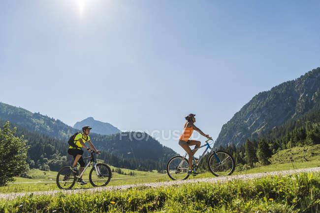 Austria, Tirol, Valle de Tannheim, pareja joven en bicicleta de montaña en el paisaje alpino - foto de stock