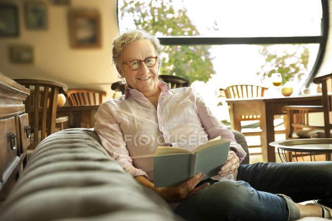 Smiling senior man in lounge room reading book — Stock Photo