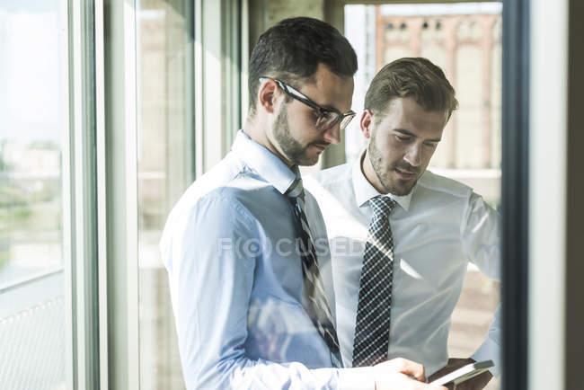 Deux jeunes hommes d'affaires avec smartphone à la fenêtre — Photo de stock