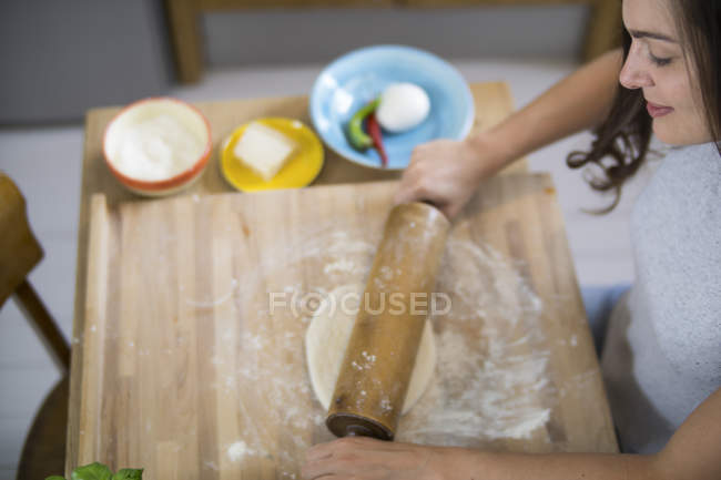 Young woman preparing pizza dough in kitchen — Stock Photo