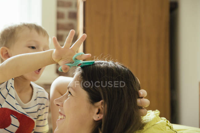 Little boy pretending to cut mother's hair at home — Stock Photo