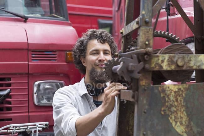 Молода людина з бородою підборіддя, регулюючи будівельних машин — стокове фото