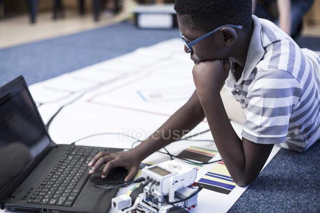 Scolaro con il computer portatile in classe di robotica test veicolo sulla pista di prova — Foto stock