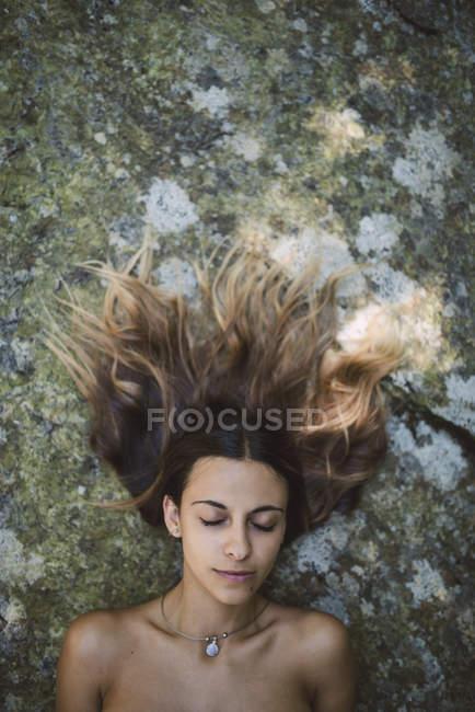 Ritratto di donna con gli occhi chiusi sdraiata su una roccia dai capelli arruffati — Foto stock