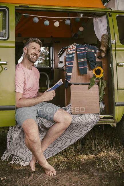 Улыбающийся читает книгу в фургоне — стоковое фото