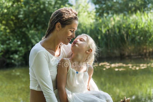 Chica besar madre en un lago - foto de stock