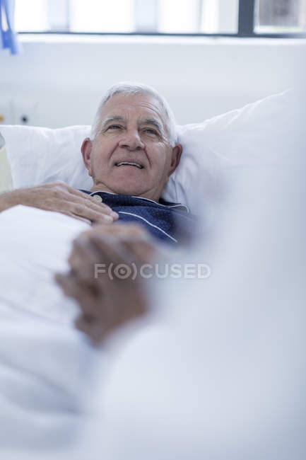 Doctor visiting hospital patient at bed — Stock Photo