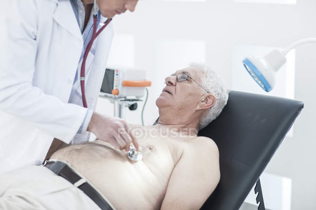 Male doctor auscultating patient in clinic — Stock Photo