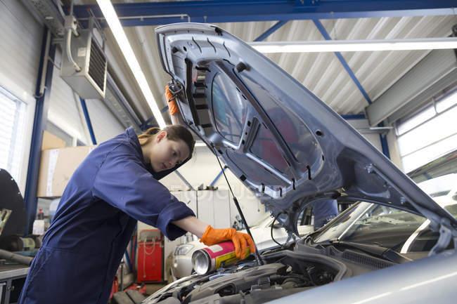 Молода жінка, що працюють в ремонт гаража, перевірка двигуна — стокове фото