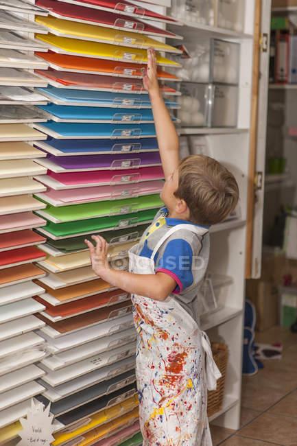 Ragazzino in un corso d'arte da scaffale con carta colorata — Foto stock