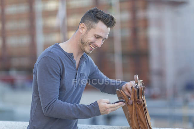 Uomo in città con valigetta e cellulare — Foto stock