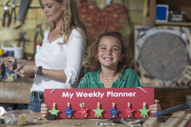 Smiling girl presenting craftwork in home garage — Stock Photo