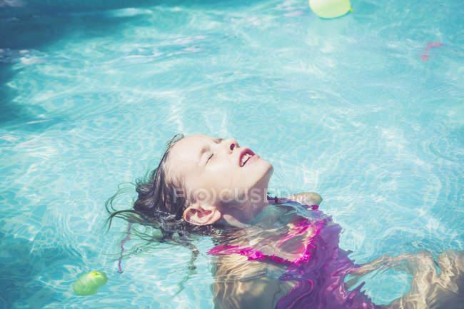 Garota na piscina flutuando na água — Fotografia de Stock