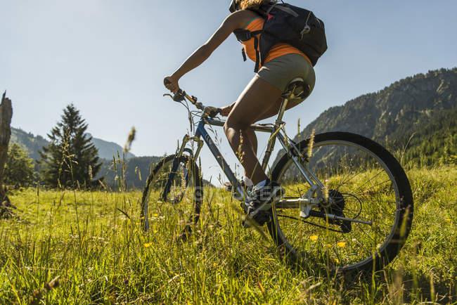 Австрия, Тироль, долина Танни, молодая женщина на маунтинбайке в пейзаже — стоковое фото