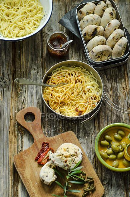 Espaguetis con pesto de tomate, parmesano y selfmade panecillos de aceitunas y tomates en una plancha de madera - foto de stock