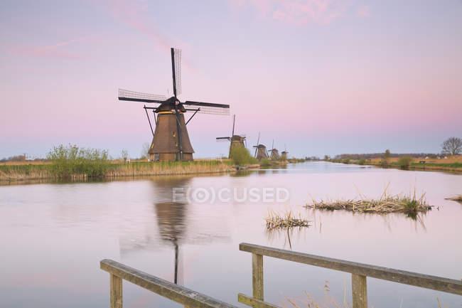 Niederlande, Kinderdijk, Kinderdijk Windmühlen in der Dämmerung gegen Wasser — Stockfoto