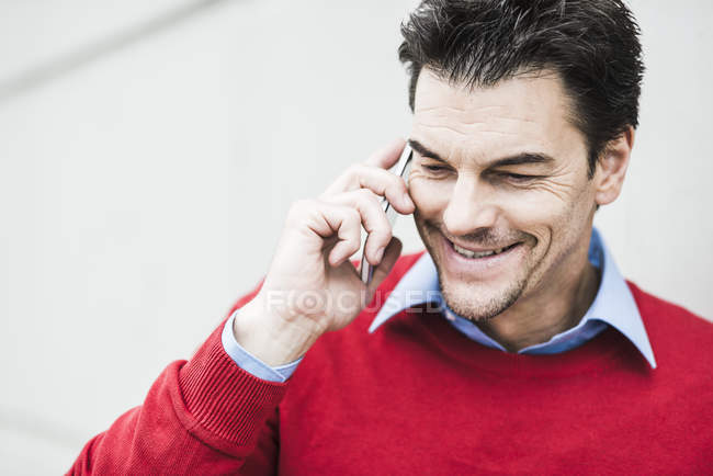 Portrait of smiling businessman wearing red pullover telephoning with smartphone — Stock Photo